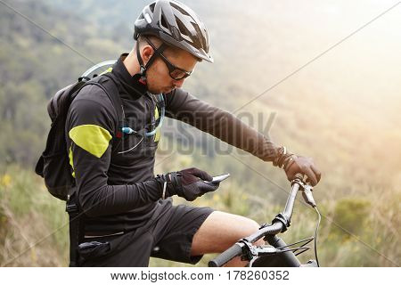 Side View Of Young European Rider Standing On Top Of Hill, Holding Mobile Phone, Using Online Applic