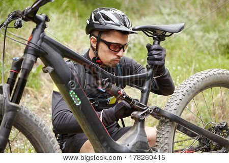 Close Up Shot Of Young Caucasian Rider Wearing Protective Gear Adjusting Seat Of His Battery-powered