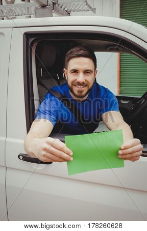 Man sitting in his van while looking out of window