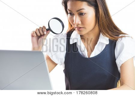 Businesswoman looking through magnifying glass and using laptop on white background