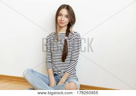 Indoor Shot Of Charming Young Woman With Messy Hair Braid Relaxing At Home After College, Sitting Cr