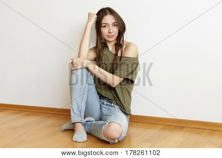 Indoor Shot Of Beautiful Teenage Girl With Messy Hair Wearing Ragged Jeans And Stylish Oversize Top