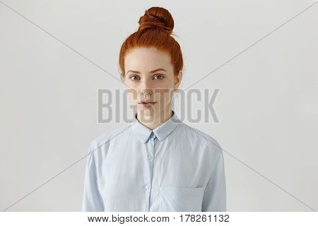 People And Lifestyle. Attractive European Student Girl With Freckles And Ginger Hair In Bun Wearing