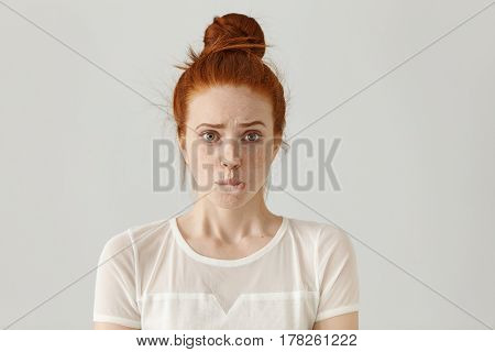 Fearful Young Caucasian Female With Ginger Hair Dressed In White Blouse Having Confused Guilty Look,