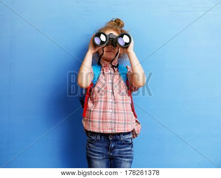Happy child girl playing with binoculars. explore and adventure concept.