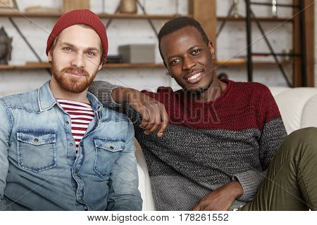 Interracial Friendship Concept. Happy African American Male In Casual Sweater Resting Elbow On His B