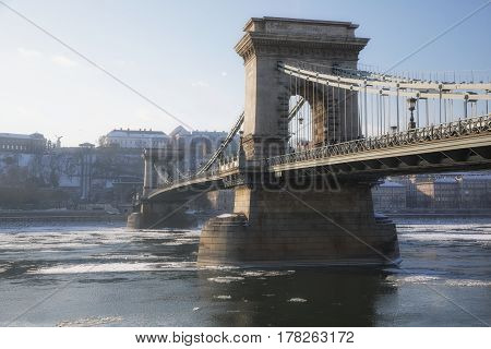 Chain Bridge at daytime with icy Danube and city