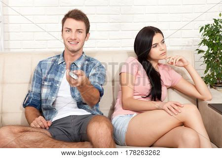 Dissapointed beautiful brunette woman in quarrel with her boyfriend. Indifferent man watching TV at home. poster
