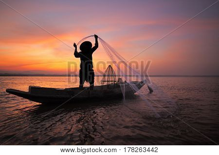 Asian Fisherman On Wooden Boat Casting A Net For Catching Freshwater Fish In Nature River In The Ear