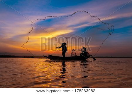 Silhouette Asian Fisherman On Wooden Boat Casting A Net For Catching Freshwater Fish In Nature River