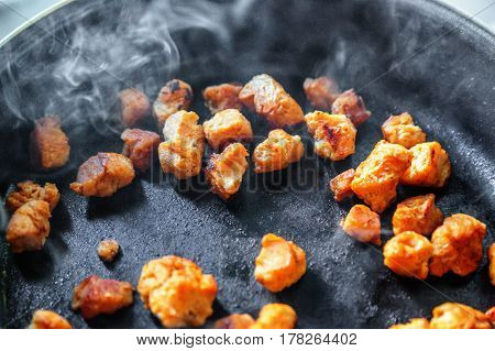 Soy meat being fried on frying pan with smoke