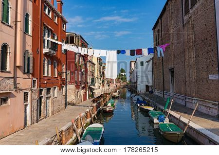 Venice Italy - September 27 2013: Washing line with laundry clothing air drying over the channel on sunny day. Venice lifestyle
