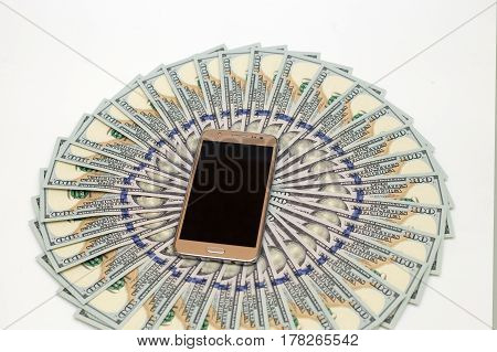 A lot of dollars are lying in a circle and a mobile phone on a white background
