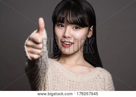Studio portraits of happy twenties Asian women with thumbs up