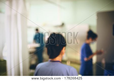 Working doctors in itensive care unfocused background.