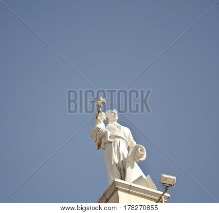 An architectural ensemble in belarus minsk an adult man holds a child on his hand who has a dove in his hand a symbol of peace. Abstraction of love and peace in a blue sky
