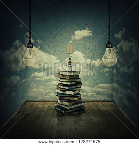 Idea concept with a boy standing on a pile of books trying to switch on the light bulbs surrounded by concrete walls with clouds texture as thinking limitations. In search of knowledge.