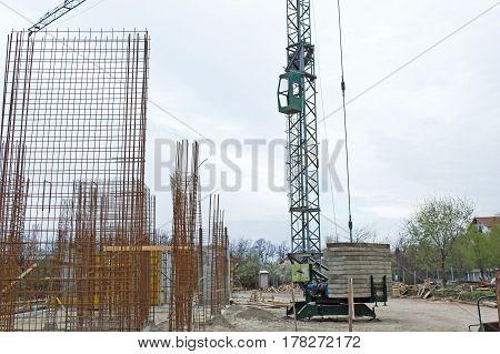 Crane at a Construction Site Against Blue Sky concrete blocks armature
