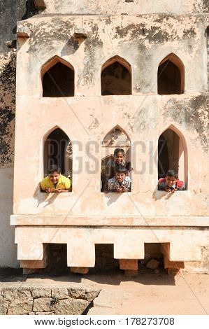 Hampi India - 12 January 2015: Boys posing on the window of Queen's bath temple at Hampi on India