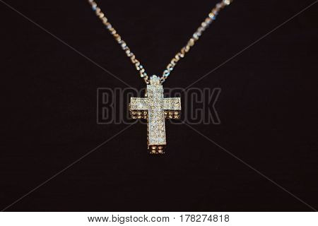 Golden necklace with cross on black background