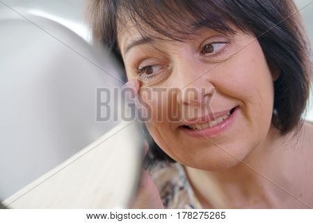 Portrait of mature woman looking at the mirror