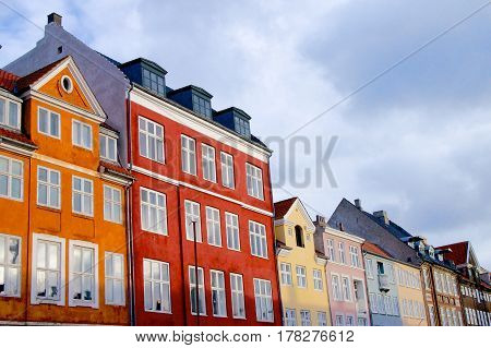Wall of Colorful Houses with Attic Windows against Blue Sky Outdoors. Copenhagen Denmark