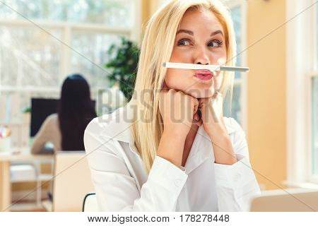 Young Woman Holding A Pen Above Lips
