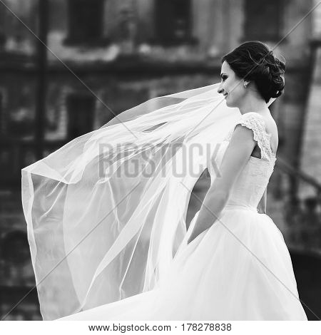 Wind blows bride's veil while she stands thoughtful behind an old castle