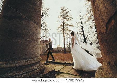 Wind Blows Bride's Dress While She Walks Behind A Ruined Cathedral