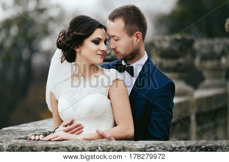 Groom Hugs From Behind A Stunning Bride Standing On The Old Gray Balcony