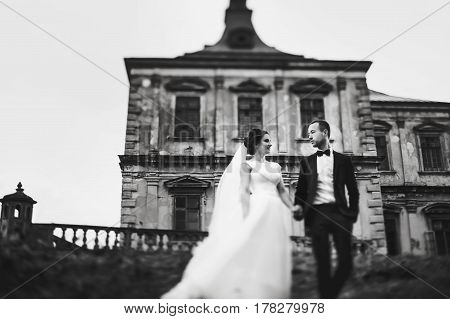 A Look From Below On A Wedding Couple Standing In The Front Of An Old Castle