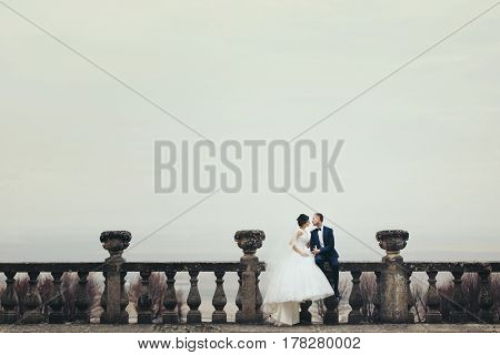 Bride And Groom Sit On The Stone Balcony With A Deep Colored Sky Over Them