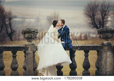 Groom Kisses A Bride Sitting With Her On The Balcony With A Great Landscape Behind Them