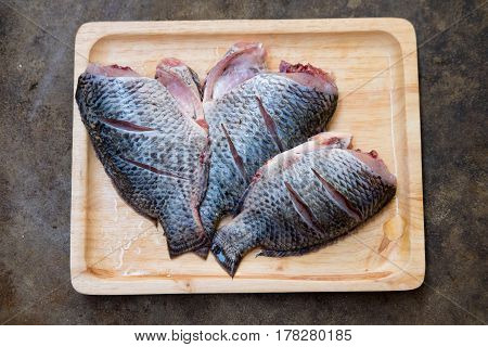 Nile tiapia fish on wooden tray. Call Pla Nil in Thai.