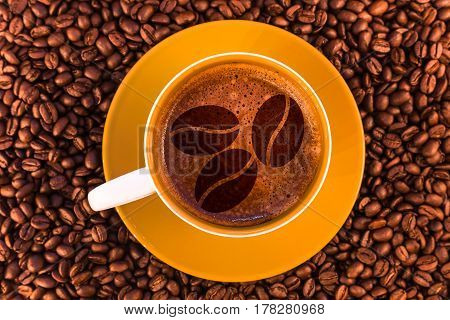 coffee beans on fresh espresso with a beautiful crema and strewn mediumly roasted coffee beans