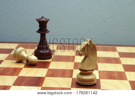 Wodden chess figures, knight, queen, pawn, brown
