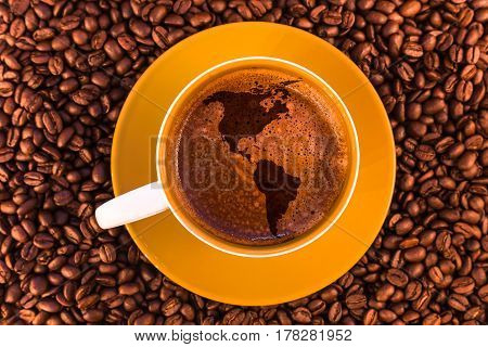 map of America on fresh espresso with a beautiful crema and strewn mediumly roasted coffee beans