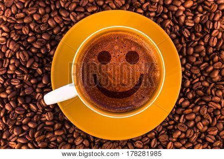 smile on fresh espresso with a beautiful crema and strewn mediumly roasted coffee beans