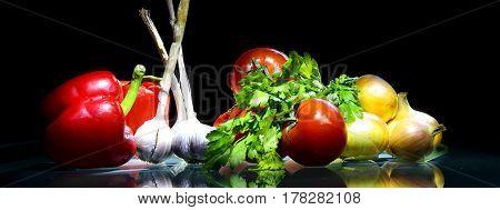 fresh onions garlic pepper against a dark background