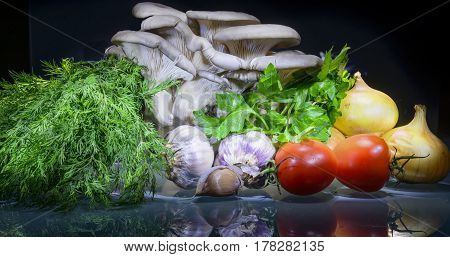 Fresh vegetables and mushrooms on the isolated black background