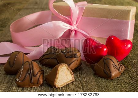 Two red hearts and chocolate candies with a gift bandaged pink ribbon with a bow close-up on a wooden background