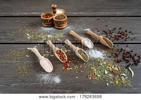 Various of spices in wooden spoons. Flat lay of spices ingredients chilli, salt, himalayan salt, savory and black pepper on grey wooden board.