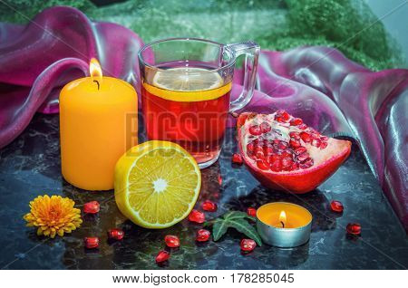 Fruit tea in a glass cup, lemon, pomegranate, burning candles on a marble surface