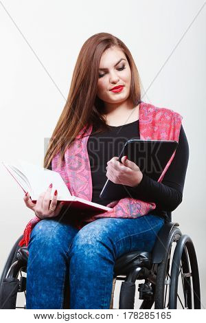Girl with tabled and book. Young female surfing reading on wheelchair. Health disability passion internet education concept.
