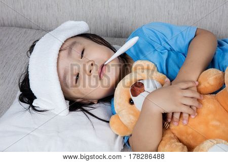Asian Chinese Girl Holding Teddy Bear For Fever Temperature Measurement