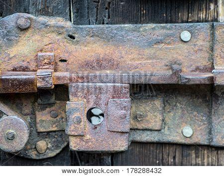 Detail of rusty iron door lock rusty old latch lever lock on a vintage wooden door