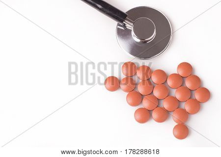 medicine and stethoscope. The stethoscope is next to the pills isolated on white background