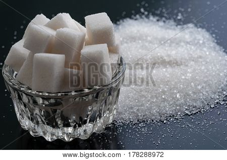 refined sugar and granulated sugar on black surface