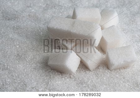 cubes of sugar on white granulated sugar background