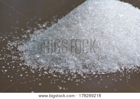 white Sugar on gray background. Heap of white granulated sugar on gray surface. Close-up